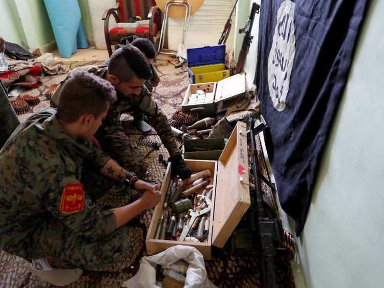 Fighters of Syrian Democratic Forces inspect weapons and munitions recovered at the former positions of the Islamic State militants