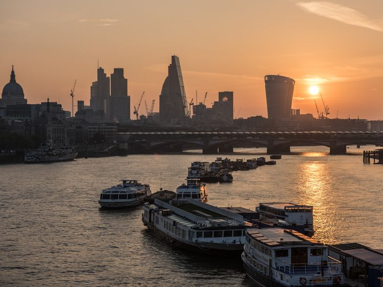 The sun rises over the City of London seen from Waterloo Bridge. Boats moored in the river Thames. The skyline includes St Paul's Cathedral, skyscrapers of The City including The Gherkin, the Cheesegrater, 20 Fenchurch Street 'Walki-Talkie'