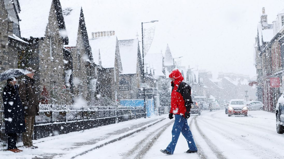 A pedestrian walks through the snow as he crosses the road during a snowfall in Pitlochry, Scotland November 24, 2017