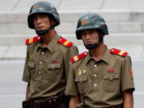 North Korean soldiers look on as South Korean and United Nation officials visit after attending a ceremony to commemorate the 64th Anniversary of the Korean War armistice agreement at Panmunjom in the the Joint Security Area on July 27, 2017 in Panmunjom, South Korea