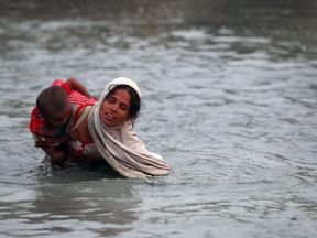A Rohingya refugee carries a child across the Naf River as they cross in to Bangladesh