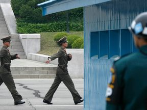 A South Korean soldier (R) watches North Korean soldiers patrol in the northern part of the Joint Security Area at the truce village of Panmunjom, in the demilitarized zone separating the two Koreas, 42 km (26 miles) northwest of Seoul April 30, 2008