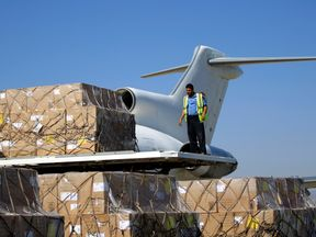A technician unloads vaccines from a plane at Sanaa airport