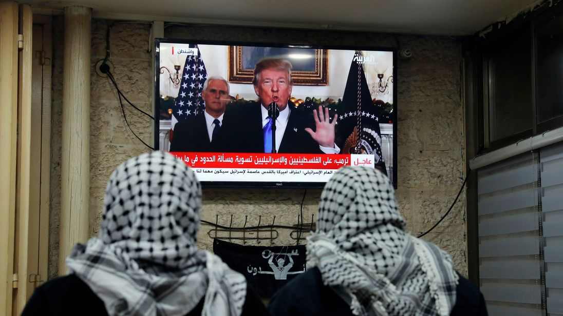 Two Palestinians watch the speech at a cafe in Jerusalam