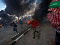 Palestinian protesters run during clashes with Israeli troops