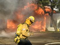 Firefighters battle to save one of many homes burning i