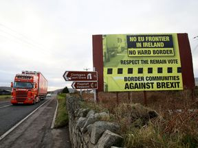 Traffic crosses the border into Northern Ireland from the Irish Republic alongside a Brexit Border poster on the Dublin road Co Armagh border
