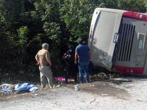 Mexican police officers and paramedics work in the scene of a road accident, where a bus driving tourists to Chacchoben archaeological zone overturned between El Cafetal and Mahahual, in Quintana Roo state, Mexico on December 19, 2017. At least eleven tourists who arrived in the Mexican Caribbean on a US cruise ship were killed and another 20 injured in a road accident on Tuesday when they were heading to an archaeological zone, the Quintana Roo state government reported. / AFP PHOTO / Manuel Je