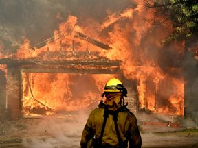 Firefighters battle to save one of many homes burning