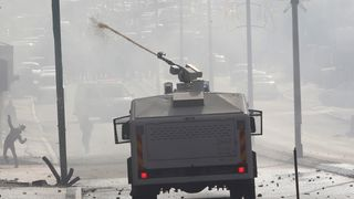 Israeli troops fire a water canon towards Palestinian protesters during clashes in Bethlehem