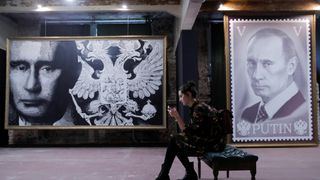 "A woman sits on a bench at the ""SUPERPUTIN"" exhibition"