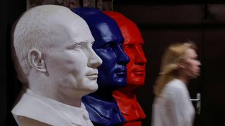 A woman walks past busts depicting Russian president Vladimir Putin in the colours of the Russian national flag