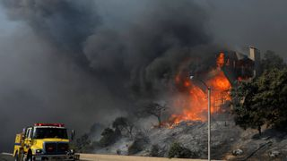 A fire crew passes a burning home during a wind-driven wildfire in Ventura, California