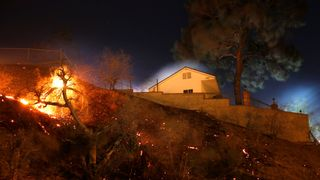 Embers continue burning near a damaged home