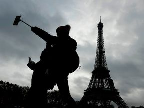 A tourist takes a selfie on the banks of the Seine river beside the Eiffel tower