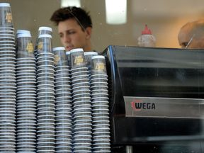 Take-away coffee cups are displayed alongside a coffee machine at the 'Met Cafe', one of the most popular cafes in the central business district of Sydney on April 20, 2010