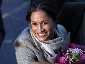 Meghan Markle receives a bouquet of flowers from a fan in Brixton