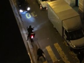 A man dressed in black makes a grab at the speeding suspect as he roars by
