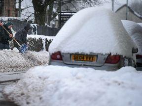 Locals try to clear snow from the front of their homes as parked cars sit covered in the white stuff in Dumfries, Scotland.