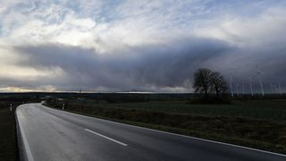 """Clouds sweep over a  road and a field with wind turbines on January 3, 2018 near Bischofsroda, central Germany, as parts of the country are hit by a stormy depression named """"Burglind"""". / AFP PHOTO / dpa / Jan Woitas / Germany OUT        (Photo credit should read JAN WOITAS/AFP/Getty Images)"""