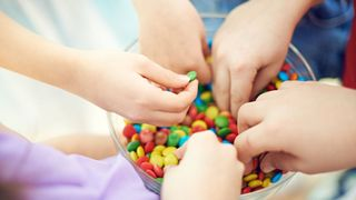 Hands of kids taking multi colored chocolate candies from bowl. Children love sweet food. They eating colorful button-shaped chocolates. Its photo illustrating happy childhood. It is perfect for using it in commercial and advertising photography, reports, books, presentation
