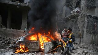 A Syria Civil Defence member carries a wounded child in the besieged town of Hamoria, Eastern Ghouta, in Damascus, Syria