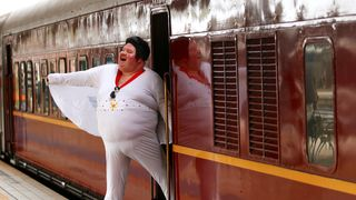 Elvis Presley impersonator Sean Wright poses next to the Elvis Express train in Sydney before it departs for the 26th annual Elvis Festival in Parkes