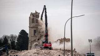 Police and visitors watch as an excavator demolishes Saint Lambertus church to make way for the expansion of a nearby open-pit coal mine in Immerath, Germany