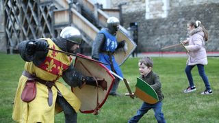 Three-year-old Rufus Murly-Gotto and a knight engage in battle, during the launch of Knight School at the Tower of London