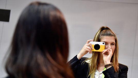 LAS VEGAS, NV - JANUARY 09: Kodak representive Paige English snaps a photo using Kodak's Printomatic instaprint camera at the Kodak booth during CES 2018 at the Las Vegas Convention Center on January 9, 2018 in Las Vegas, Nevada.