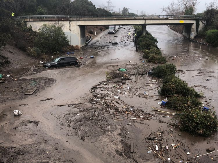 Abadoned cars stuck in flooded water on the freeway after a mudslide in Montecito, California