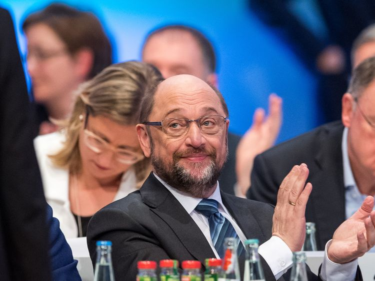 Martin Schulz clapped as party members voted to enter coalition talks with Mrs Merkel