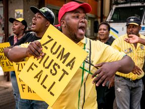 Supporters of the ANC Deputy President Cyril Ramaphosa hold placards and chant slogans outside the ANC party headquarter in Johannesburg