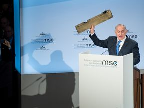 Israeli Prime Minister Benjamin Netanyahu holds up a remnant of what he said was a piece of Iranian drone which was shot down in Israeli airspace. Lennart Preiss/MSC Munich Security Conference/Handout via REUTERS