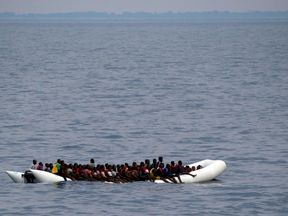 """Migrants on a dinghy are seen being rescued by """"Save the Children"""" NGO crew from the ship Vos Hestia in the Mediterranean sea off Libya coast"""