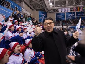 A man impersonating North Korean leader Kim Jong Un gestures as he stands before North Korean cheerleaders attending the Unified Korean ice hockey game against Japan during the Pyeongchang 2018 Winter Olympic Games at the Kwandong Hockey Centre in Gangneung on February 14, 2018.