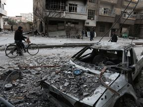 Syrians walk along a street in eastern Ghouta