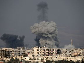 Smoke plumes rise following a regime air strike in the rebel-held town of Hamouria, in the besieged Eastern Ghouta region