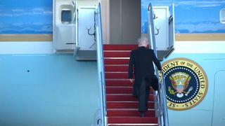Donald Trump's bald patch exposed as he boards Air Force One.
