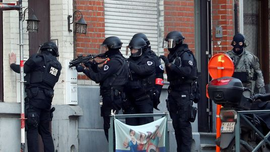 Belgian police special forces prepare to enter a building after an area of the Forest commune was closed by Belgian police and special forces, in Brussels