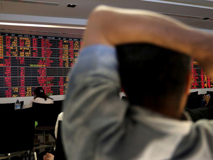 People monitor a stock index board at a bank in Bangkok, Thailand