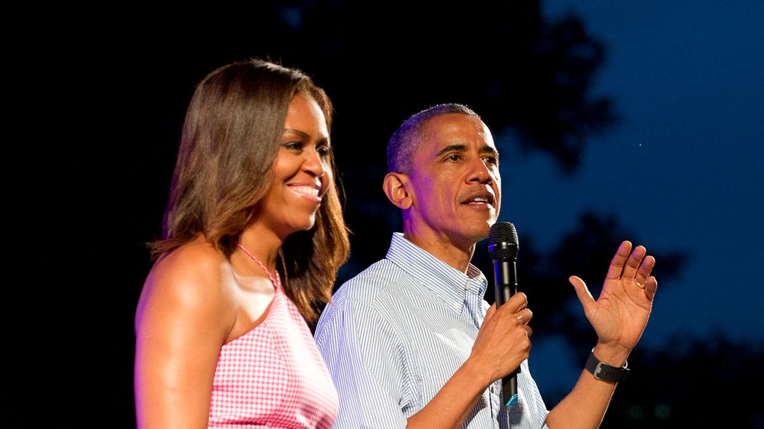 U.S. President Barack Obama (R), accompanied by first lady Michelle Obama, gives remarks to members of the military and White House staff who were invited to the South Lawn of the White House on July 4, 2015 in Washington, DC