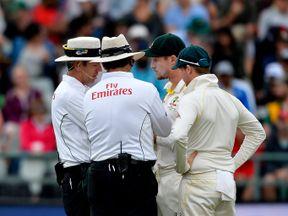 Umpires speak to Australian cricketers Cameron Bancroft and Steven Smith