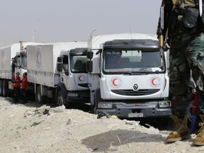 A Syrian soldier stands guard as Syrian Arab Red Crescent vehicles carrying aid wait at the al-Wafideen checkpoint on the outskirts of Damascus neighbouring the rebel-held Eastern Ghouta region before delivering aid to the rebel-held enclave