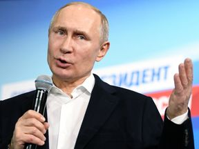 Vladimir Putin speaks during a meeting with supporters at his campaign headquarters