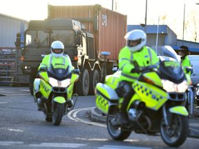 Police officers escort an army truck, carrying a freight container laden with the car of Sergei Skripal, as it is driven from the Churchfields industrial estate in Salisbury, southern England, on March 16, 2018