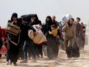 People walk with their belongings as they flee the rebel-held town of Hammouriyeh, eastern Ghouta