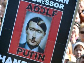 People hold placard portraying Russian President Vladimir Putin as Adolf Hitler