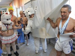 Members of the winter swimming club 'Polar Bear' visit a polling station to cast their votes during the presidential election in the Russian city of Barnaul