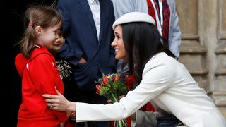 Britain's Prince Harry's fiancee Meghan Markle receives a bouquet of flowers after attending the Commonwealth Service